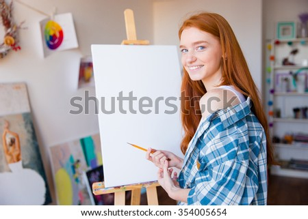 smiling beautiful woman painter making sketches on blank canvas stock photo © deandrobot