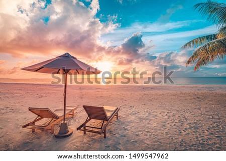 Tropical island in sea. Palm trees, sand, sun lounger and parasol Stock photo © orensila