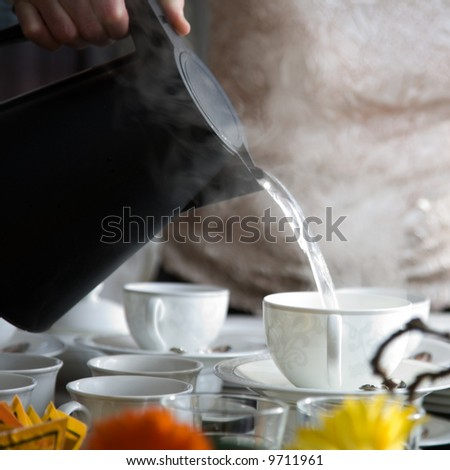 Woman pouring a Cup of hot steaming tea in the restaurant. Winter leisure, cold weather,  drink Stock photo © frimufilms