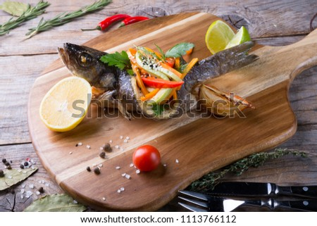 Baked fish stuffed with vegetables on a white plate on a wooden  Stock photo © Yatsenko