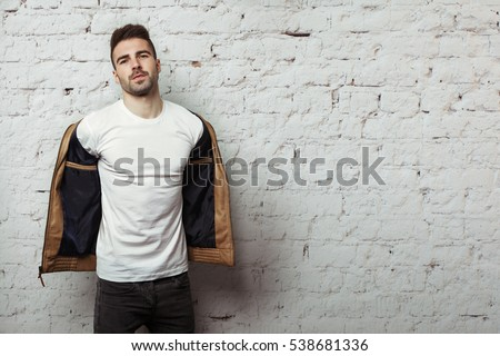 attractive young man in leather jacket taking off his sunglasses Stock photo © feedough