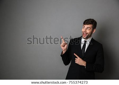 aantrekkelijk · zakenman · klassiek · zwart · pak · wijzend · vinger - stockfoto © deandrobot
