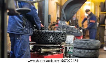 Skilled auto mechanic replacing the rims of a car in a trendy repair shop Stock photo © Kzenon