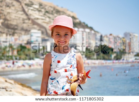 Girl 6-7 years old on Postiguet beach, looking at camera. Santa Barbara castle fortification, swimmi Stock photo © amok