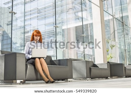 Full length image of business woman in formal wear sitting on ch Stock photo © deandrobot