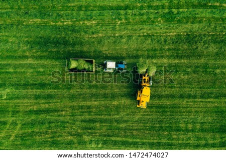 Aerial view agricultural machinery tractor stacks bales of hay in the field. Photo from drone. Top v Stock photo © artjazz