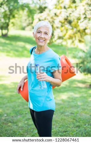 Senior woman holds fitness mat on her back in the park and prepa Stock photo © boggy