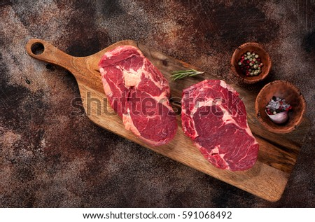 Raw sirloin beef steak on rusty background. Salt and pepper with fresh rosemary and bowl of oil.Spac Stock photo © DenisMArt