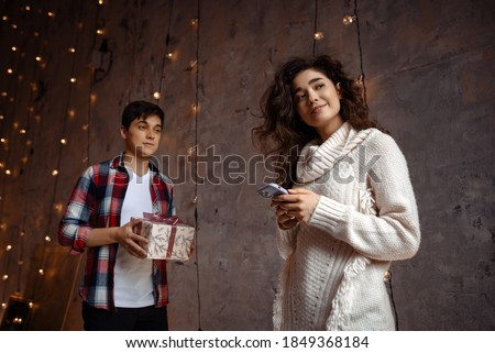 excited young loving couple in sweaters using mobile phone listening music isolated over beige backg stock photo © deandrobot