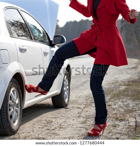 Angry woman kicks car wheel after car accident or some broken sp Stock photo © Nobilior