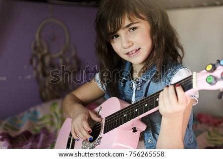 Little attractive girl with his guitar on his knees on the bed in the room Stock photo © Lopolo