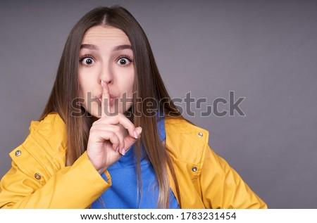 Image of blonde woman 20s wearing yellow raincoat keeping palms  Stock photo © deandrobot