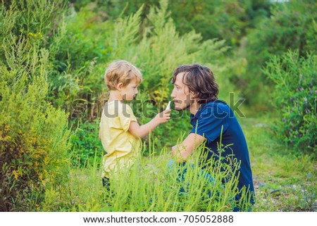 Father and son use a spray from an allergy because of an allergy to ragweed Stock photo © galitskaya