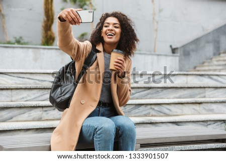 Image of european woman wearing jacket holding takeaway coffee i Stock photo © deandrobot