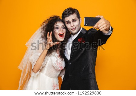 Photo of joyful zombie couple bridegroom and bride wearing weddi Stock photo © deandrobot