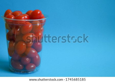 fresh organic cherry tomatoes in a plastic cup with blue straw on a color background of the year 201 stock photo © artjazz