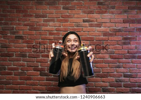 Image of amusing hip hop girl 20s, standing against brick wall w Stock photo © deandrobot