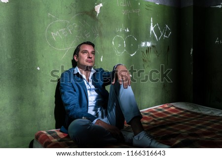 Depressed young man sitting on a mattress in a dark prison cell during custody Stock photo © Kzenon