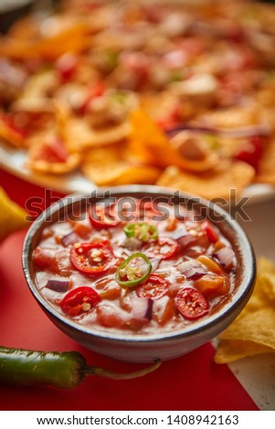 Close up on hot tomato dip in ceramic bowl with various freshly made Mexican foods Stock photo © dash