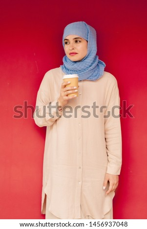 Young stylish Arabian woman in hijab and casualwear having hot drink Stock photo © pressmaster