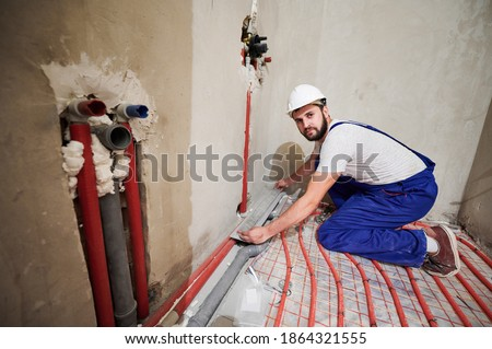 Stock photo: Young plumber or technician installing or repairing system of water filtration