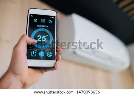 Température air chambre écran smartphone main humaine Photo stock © pressmaster