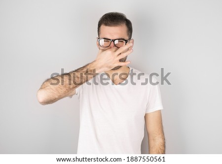 Young man with disgust on his face pinches nose, something stinks, very bad smell in swimming pool b Stock photo © galitskaya