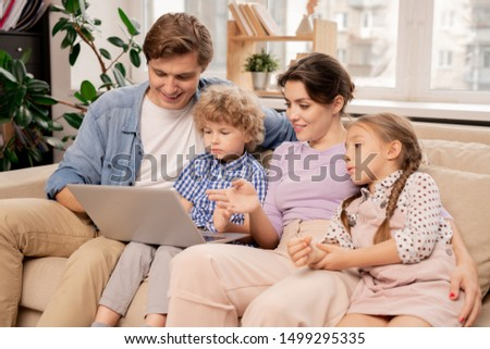 contemporary couple and two kids discussing movie while watching it at leisure stock photo © pressmaster