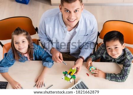 Overhead of schoolkids looking at camera in classroom of elementary school Stock photo © wavebreak_media