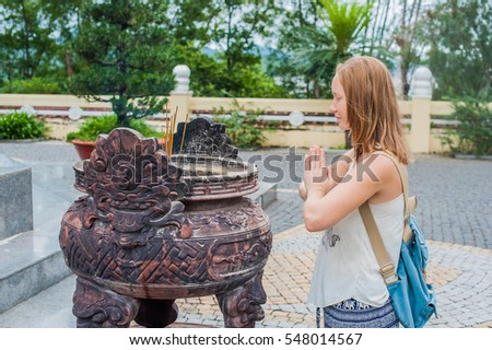 Young woman Traveler praying in polite action with incense sticks at buddhism temple in Vietnam Stock photo © galitskaya