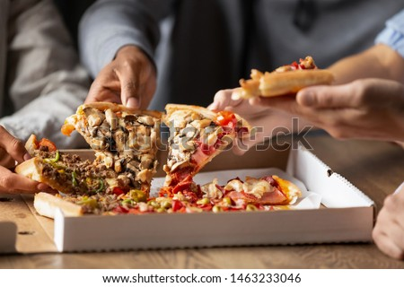 Multiracial female friends eating fast food at a table in the di Stock photo © boggy