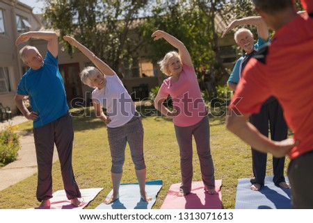 Front view of trainer training senior people in performing exercise with elastic band and ball at pa Stock photo © wavebreak_media