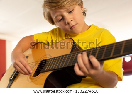 Front view of handsome Caucasian boy playing guitar in a classroom at elementary school Stock photo © wavebreak_media