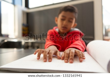 Stock photo: Front view of mixed-race blind schoolboy hands reading a braille book in classroom at elementary sch