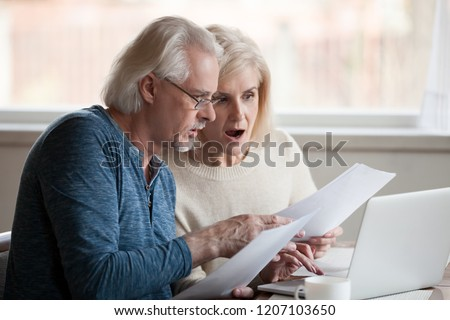 Worried couple read letter from bank, get notification for paying bills, have sad looks, sit on benc Stock photo © vkstudio