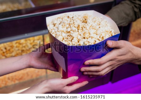 Hands of young female vendor passing big purple paper box full of popcorn to guy Stock photo © pressmaster
