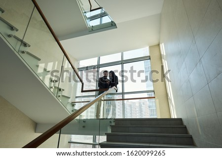 Two young colleagues in formalwear standing by railinigs between staircases Stock photo © pressmaster