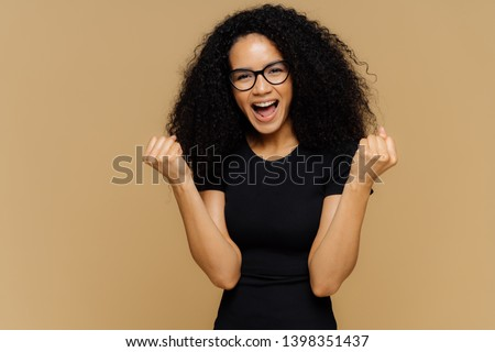 Stock photo: Yeah, I finally did it! Optimistic lovely dark skinned curly woman raises clenched fists, exclaims f