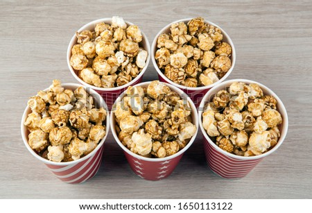 five red cardboard cup in a row with sugar popcorn on a wooden t Stock photo © mizar_21984