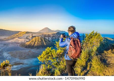 Young man meets the sunrise at the Bromo Tengger Semeru National Park on the Java Island, Indonesia. Stock photo © galitskaya