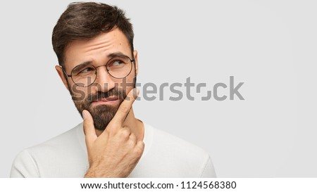 Close up portrait of attractive male with stubble, wonders something and looks with surprisement asi Stock photo © vkstudio