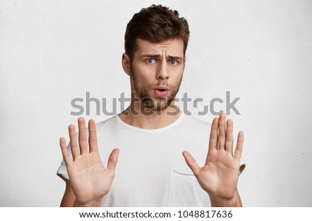 Horizontal shot of handsome bearded male shows palms at camera,  Stock photo © vkstudio