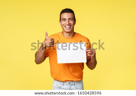 Good-looking young masculine man in orange t-shirt giving advice where buy online, pointing down smi Stock photo © benzoix