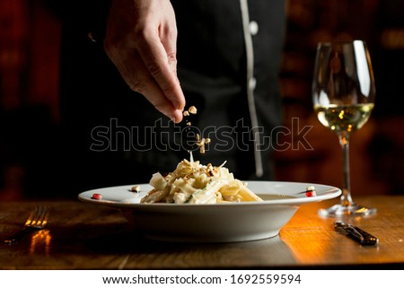 Adding hazelnuts to penne with chicken and spinach in parmesan s Stock photo © boggy