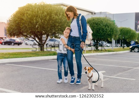Affectionate mother embraces small daughter, have outdoor stroll together with their favourite pet,  Stock photo © vkstudio