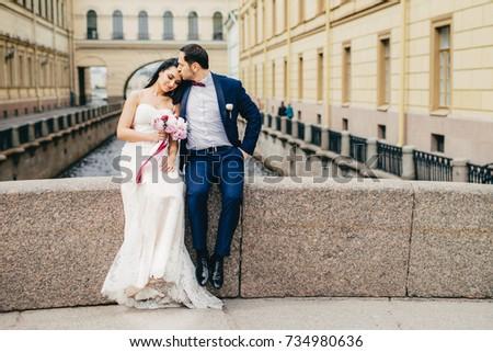 Affectionate married couple sit on bridge togetherm enjoy fresh air, have good relationship, kiss ea Stock photo © vkstudio