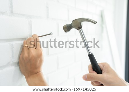 Handyman hammering a nail for House with siding panels, construc Stock photo © snowing