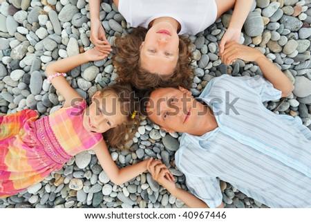Stock photo: Happy family with little girl lying on stony beach, having joine