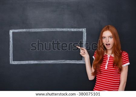 amazed woman pointing on copyspace inside frame drawn at blackboard stock photo © deandrobot