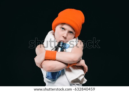 Boy in hat with towel on neck hugging bottle and drinking water isolated on black Stock photo © LightFieldStudios